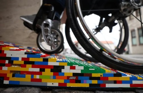 Wheelchair rolling up colourful Lego ramp